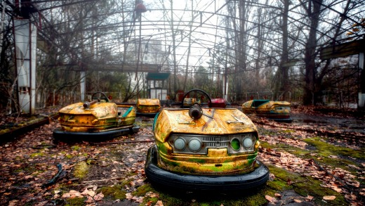 An abandoned collection of dodgem cars sprouting weeds in Chernobyl.