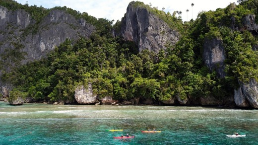 Paddling past high limestone walls on Quoy Island, northern Raja.