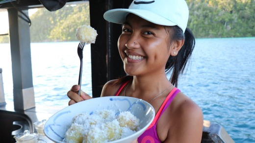 Ega, one of the crew, offering us a post-paddling snack of coconut balls.