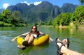 A couple drift down Nam Song River in a tube surrounded by karst scenery in Vang Vieng, Laos.