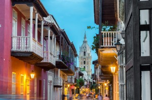 Street view of Cartagena, Colombia after sunset with cathedral visible in the background.