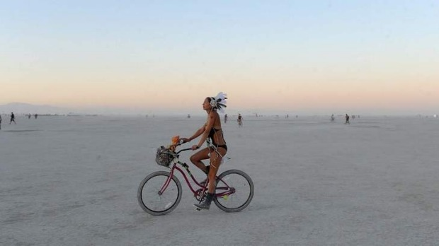 A woman rides a bicycle on the playa after sunset at the Burning Man festival.