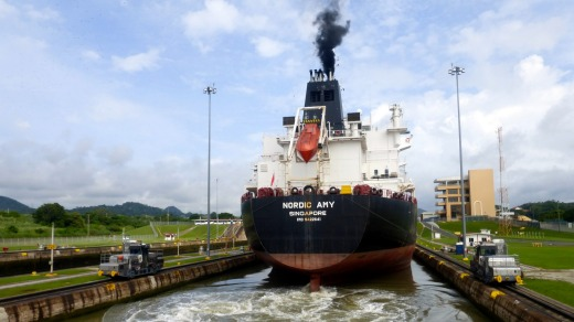 """A tanker passing through Miraflores lock, guided by electronic """"mules""""."""