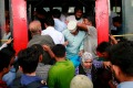 Locals try pile into an overcrowded bus in Bangladesh.