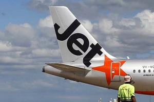 An airport worker stands in front of a Jetstar passenger plane at Avalon Airport in Melbourne in this March 19, 2010 ...
