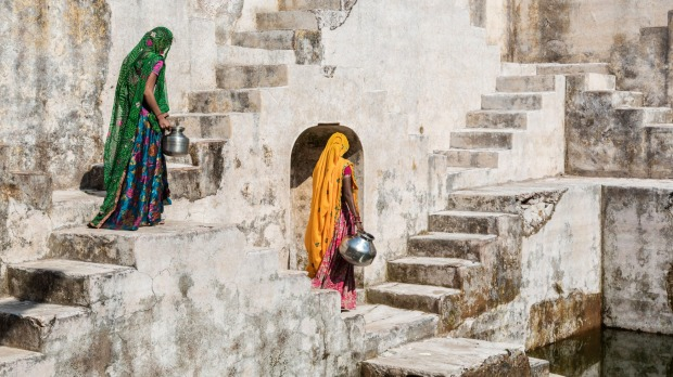 Women in saris carrying water at step well, Jaipur.