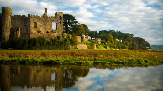 Laugharne castle in West wales with Dylan Thomas' Boathouse in the distance.