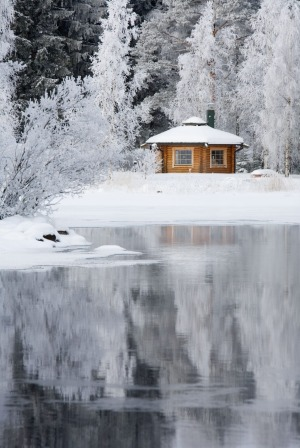 A wooden sauna cabin on a riverbank in Finland.