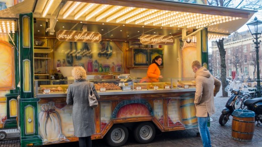 People buying fresh oliebollen at a street vendor in The Hague, Netherlands.