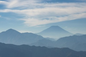 View of Mount Fuji wrapped in misty clouds seen from Mount Takao, Japan.