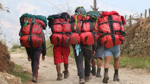 Porters carrying our red duffel bags.