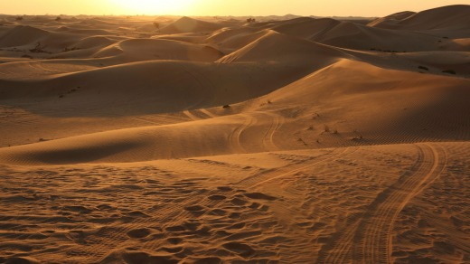 Four wheel drive tracks and sunset in the desert of Abu Dhabi in the United Arab Emirates.