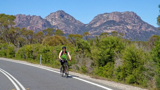 Cycling on Frecyinet Peninsula, with the Hazards mountains behind.