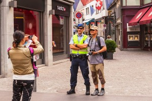 Tourists take photos with a policeman in Zurich. Lonely Planet's guide to Switzerland suggests police there engage in ...
