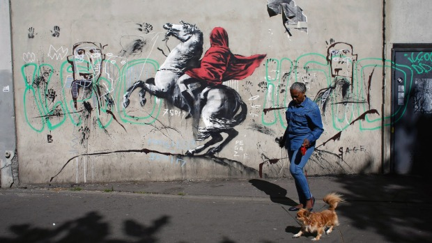 A woman walks past a graffiti attributed to street artist Banksy.