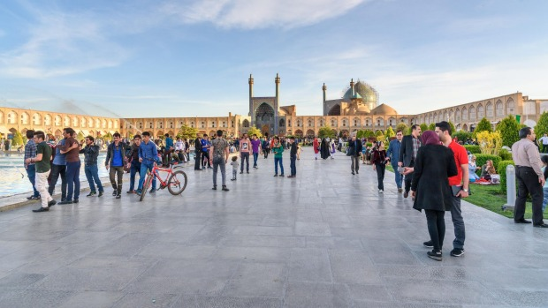 People socialise at Naghsh-e Jahan Square, with  Imam Mosque in the background.