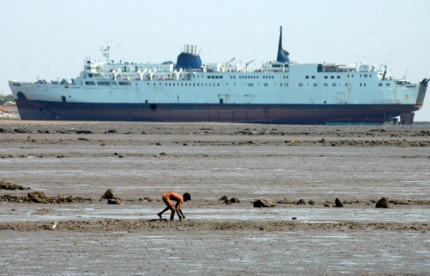 A man hunts for fish and crabs, as decommissioned ship lays at a ship breaking yard in Alang. When ships get truly ...