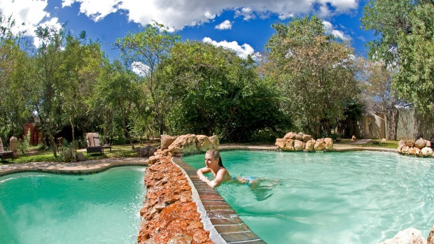 Sanctuary Chobe Chilwero; A guest enjoying the pool.