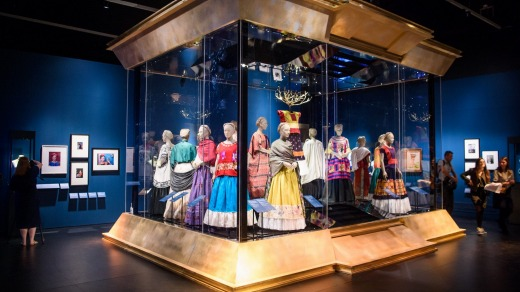 Visitors look at mexican traditional dresses owned by Frida Kahlo, part of the Frida Kahlo: Making Her Self Up ...