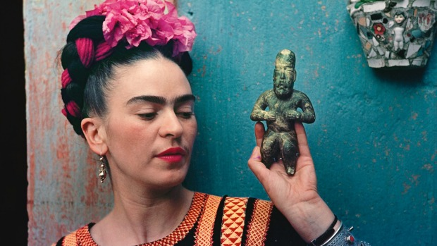 Frida Kahlo with Olmec figurine, cira 1939. Photograph by Nickolas Muray.