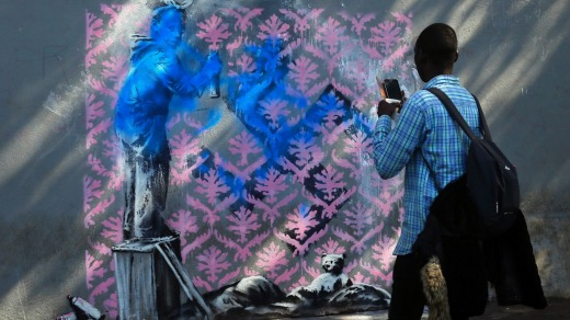 This work on a street in northern Paris where migrants often sleep rough, shows a black girl spray-painting pink ...