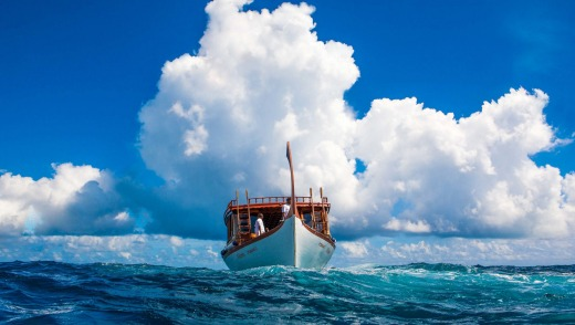 Sail between islands on a traditional wooden dhoni in the Maldives.