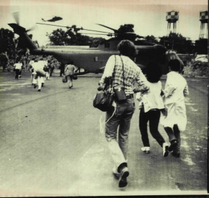 Americans and Vietnamese run for a US Marine helicopter during the evacuation of Saigon Tuesday. April 29, 1975.