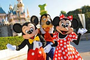 Mickey Mouse, Goofy and Minnie Mouse welcome visitors in front of Sleeping Beauty Castle at Disneyland.