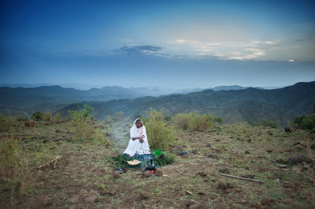 Woman performing a Traditional Coffee Ceremony on a hillside at sunrise outside Lalibela Ethiopia Horn of Africa.