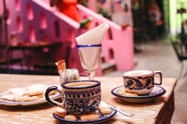 Cup of coffee in traditional talavera pottery mug at pink cafe in Puebla, Mexico.