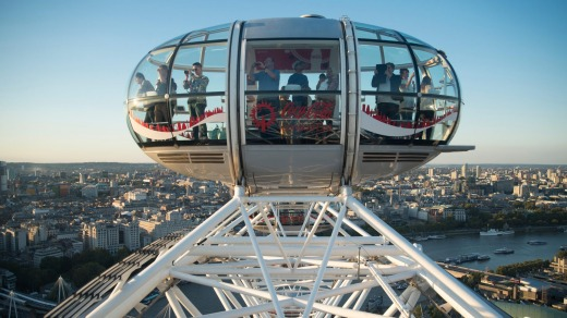 The London Eye ferris wheel overlooks the Thames River.