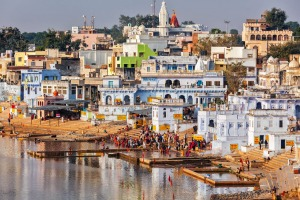 Pushkar's white cubist buildings cram the lake's edge and are framed by barren brown hills.