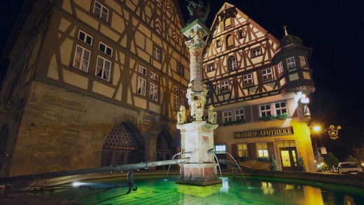 Historic buildings with fountain in the foreground at night in Rothenburg Ob Der Tauber, Germany.