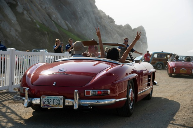 A woman raises her arms to celebrate her arrival at Morro Rock. The Dream Drive celebrates the reopening of Highway 1, ...