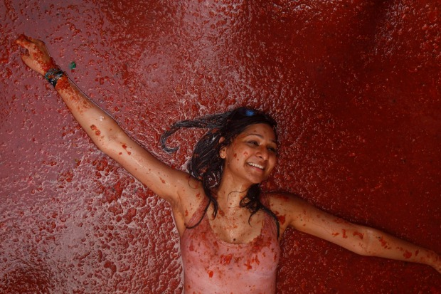 A reveller lays in tomatoes during the annual 'Tomatina', tomato fight fiesta, in the village of Bunol, 50 kilometres ...