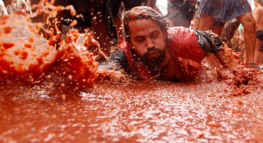 Revellers throw tomatoes at each other, during the annual 'Tomatina', tomato fight fiesta, in the village of Bunol, 50 ...