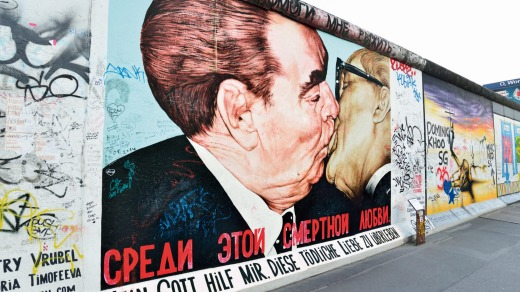 Soviet leader Leonid Brezhnev kisses East German leader Erich Honecker on the East Side Gallery section of the Berlin Wall.