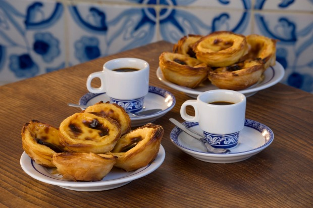 Custard tarts, on a cafe table with bica coffees; Belem, Lisbon.