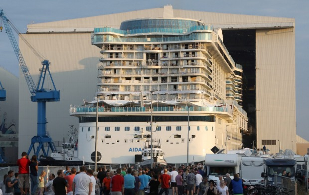 Spectators watch as the new cruise ship leaves dry dock .