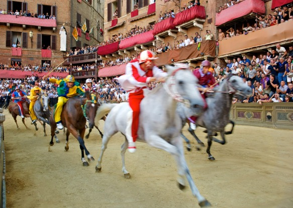 The Palio, Italy: The main square of Siena, surrounded by buildings, with sharp angles and elevation rises, is ...