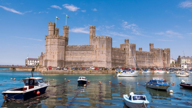 P793N7 Caernarfon Castle Wales, UK. Sunny day in summer, with boats in the harbour. str22-trav10castles