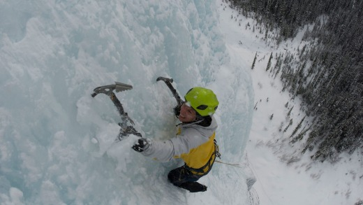 An ice climber ascends a frozen waterfall in the Canadian Rocky Mountains.
