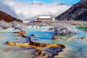 The multi-coloured pond with Huanglong Middle Temple on background in the Huanglong National Park.