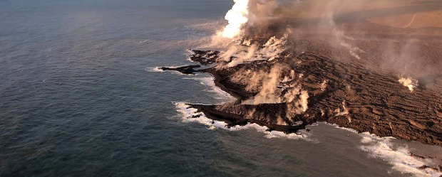 Lava from Kilauea Volcano  enters the ocean, with a resulting laze plume, at Kapoho on the island of Hawaii.