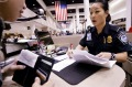 A US Border Protection officer checks the passport and paperwork of a visitor at Los Angeles International Airport.