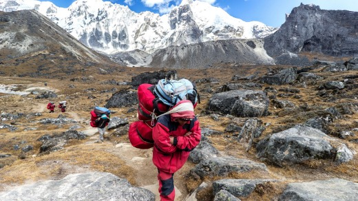 Porters with heavy loads after crossing Cho La Pass.