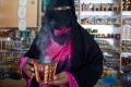 A veiled vendor at a frankincense shop at Al-Husn Souq in Salalah.