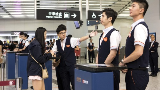 An attendant directs a passenger inside West Kowloon Station.