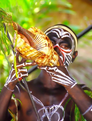 Trobriand Island warrior blows on a shell horn at Alotau, Papua New Guinea.
