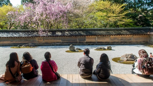 Japanese tourists enjoy tranquility at Ryoanji Temple. This Zen Buddhist temple is famous for its rock garden.